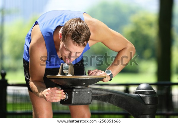 Sport man drinking water from public park fountain. Young male active adult thirsty after run or workout using the water fountain to drink and re-hydrate in Central Park, Manhattan, New York, USA.