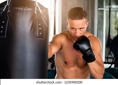 a sport man exercise in fitness gym with boxing activity and using hand box sack target