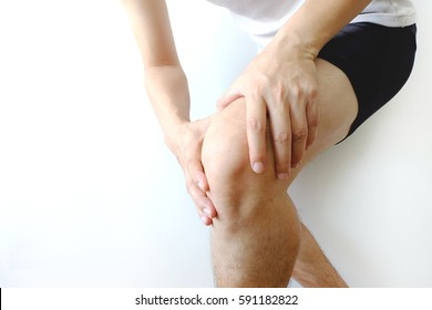 Sport man with knee pain and holding hand on her knee, on white background, healthy care and sport concept.