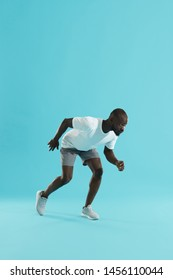 Sport. Man runner standing in running start pose on blue color background. Sporty male athlete in stylish sports wear preparing to run at studio