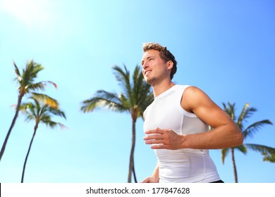 Sport man running. Male athlete runner jogging in compression t-shirt top training on palm trees beach. Fit handsome male fitness model jogging alone training for marathon run. Man in his twenties.