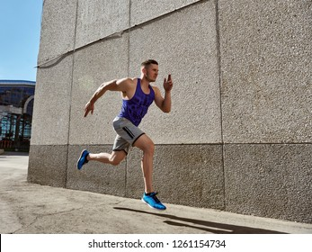 sport man starting running. Young man jogging front cement wall.