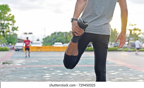 Sport man is stretching leg muscle before to exercise or running in the central park at sunset time to prevent injury,good healthcare