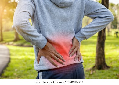 Sport man suffering from backache at park outdoors, Lower back pain concept