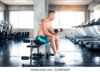 A sport man training fitness and using or carry dumbbell in gym
