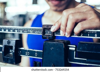 Sport man weighing himself on balance weight scale at the gym
