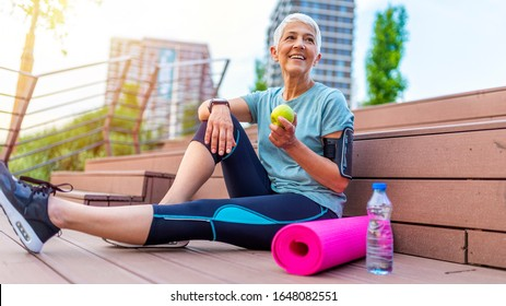 Sport mature woman sitting and resting after workout or exercise and eating apple on floor. Relax concept. Strength training and Body build up theme. Beautiful sporty woman eating apple