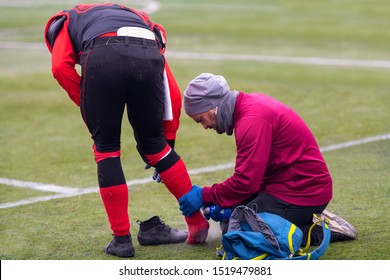 Sport medicine in action  Sports doctor using freezing spray while anesthetizing injured foot of a professional american football player on the stadium field