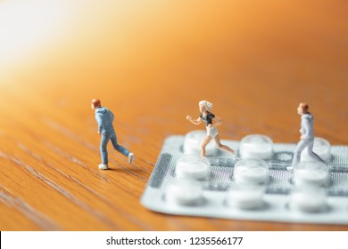 Sport, medicine and health care concept. Group of man and woman miniature figure running on pills or tablets in blister packs.