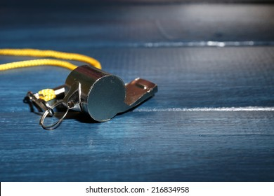 Sport metal whistle on color wooden background