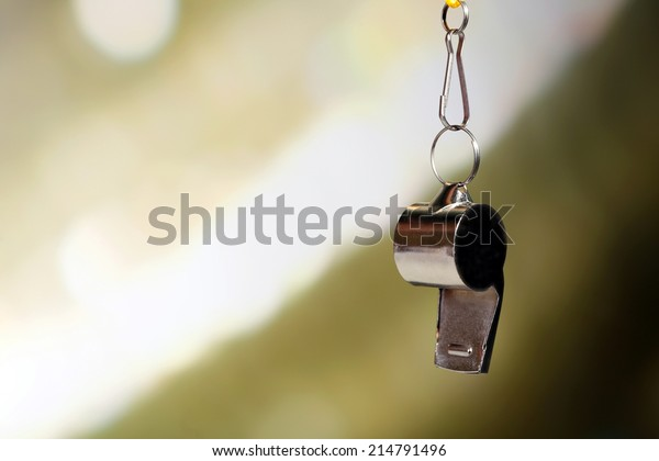 Sport metal whistle on color background