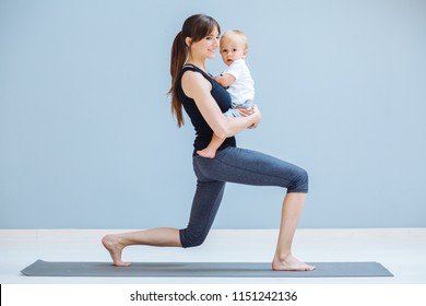 Sport, motherhood and active lifestyle concept - side view of young mother doing yoga with toddler baby at home. Lounge exercise.