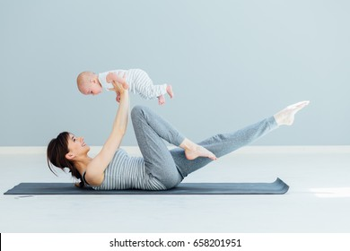 Sport, motherhood and active lifestyle concept - side view of young mother workout together with her baby over gray wall background. Mother having fun and playing with her little son.