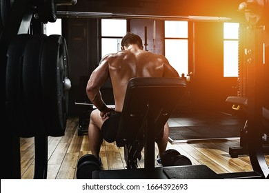 Sport motivation. gym theater. Muscular guy bodybuilder doing exercises with dumbbells in the gym. Athletic body, healthy lifestyle, fitness motivation, body positive.
