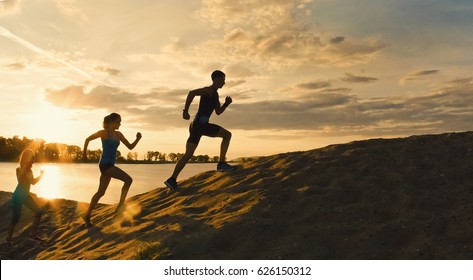 Sport motivations -group of athletes - two girls and a guy are fleeing the mountain, near river at dusk