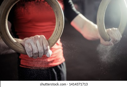 Sport. Muscle-up exercise young man workout at the gym on gymnastic rings with magnesia on the hands. Grop close-up view.