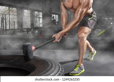 Sport muscular man hitting wheel tire with hammer sledge in the gym. Sports training