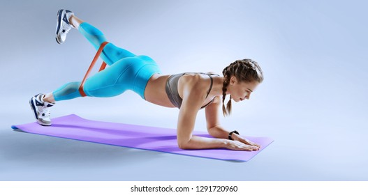 Sport. Muscular woman on a plank position use fitness gum. Muscular and strong girl exercising. Fitness exercising with expander.