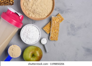 Sport nutrition with vegetarian protein powder for cocktail and creatine scoop on concrete background top view flat lay