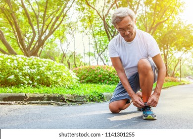 Sport old Man or Senior runner Tying Shoelaces getting ready jogging in park