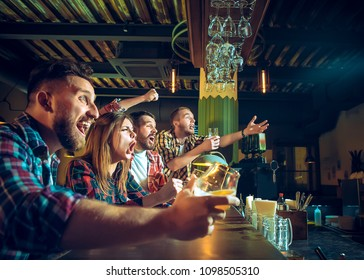 Sport, people, leisure, friendship, entertainment concept - happy male and female football fans or good yuong friends drinking beer, celebrating victory at bar or pub. Human positive emotions concept