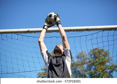 sport and people - soccer player or goalkeeper catching ball at football goal on field