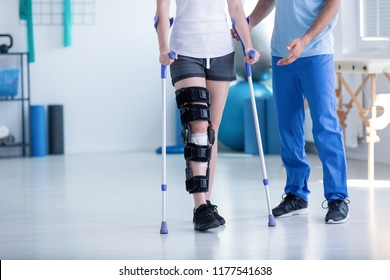 Sport physiotherapist and patient with leg injury during training with crutches