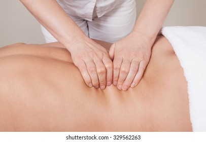 Sport professional massage on a muscle group (erector spinae muscles) of a woman's back