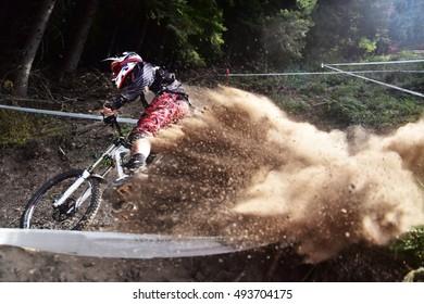 Sport race Mountain biker extreme and fun downhill track. Dirt splash. Focus on the biker, defocus on the dirt
