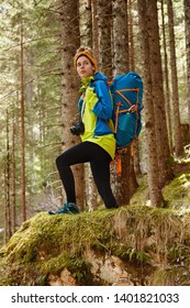 Sport, recreation and camping concept. Full legth shot of active female hiker overcomes long distance, dressed in comfortable clothes, carries big touristic backpack, photocamera, poses in forest