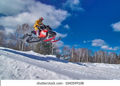 Sport red snowmobile jump. Clear sunny winter day. Concept quick movement. Copy space.