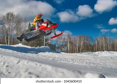 Sport red snowmobile jump. Sunny winter day with blue sky. Concept quick movement. Copy space.