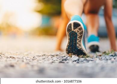 Sport. Runner feet running on road close up on shoe.