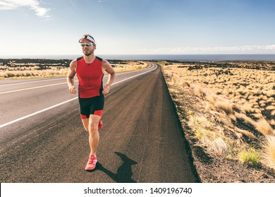 Sport runner man athlete running in triathlon tri suit training for Iron man on Hawaii. Fit male triathlete exercising cardio at sunset on road in nature landscape on Big Island, Hawaii.