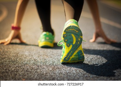 Sport runner in a start position on the running track with a shadow on the lane. The close-up shot covers the back of the feet with sneakers, legs, and hands. It's a metaphor for starting initiatives.