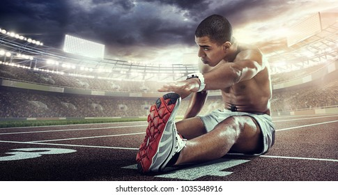 Sport. Runner stretching on the the start line. Dramatic view.