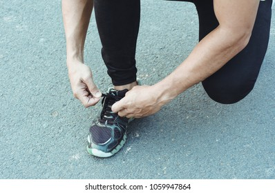 Sport runner tying laces of running shoes before exercise. Healthy and lifestyle concept.