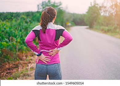 sport runner woman cramps in back and feel pain, athletic young Asian girl in sportswear touching her waist flank painful injury outside after exercise workout in nature road. Sports injuries concept