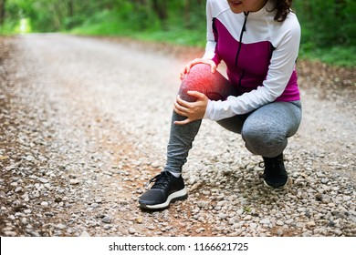 sport runner woman cramps in leg and feel pain, athletic young Asian girl in sportswear touching her knee ankle painful injury outside after exercise workout in nature road. Sports injuries concept