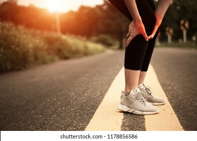 sport runner woman cramps in leg and feel pain, athletic young Asian girl in sportswear touching her muscles ankle painful injury outside after exercise workout in nature road. Sports injuries concept