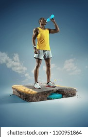 Sport. Runner. Young muscular build man drinking water of bottle after running, attractive athlete resting after workout outdoors, fitness and healthy lifestyle concept. Standing on the road.