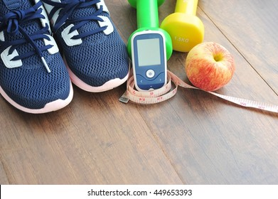 Sport shoe with glucose meter,fruits and dumbbells for using in fitness, concept of diabetes, Exercise in Diabetes Patients concept.