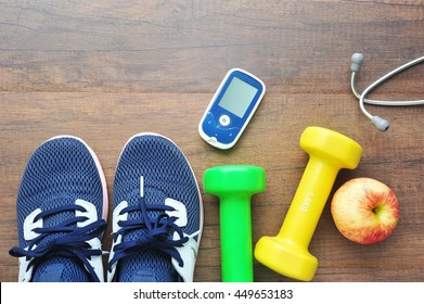 Sport shoe with glucose meter,stethoscope,fruits and dumbbells for using in fitness, concept of diabetes, Exercise in Diabetes Patients concept.