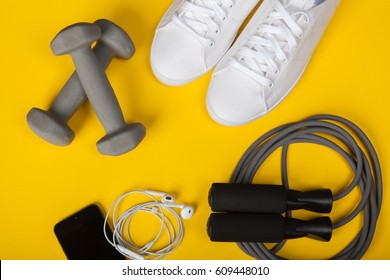 Sport shoes, dumbbells, mobile phone and skipping rope on yellow background. Top view. Fitness, sport and healthy lifestyle concept.