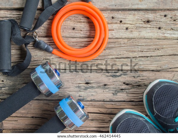 Sport shoes, Dumbbells and resistance bands on wooden background