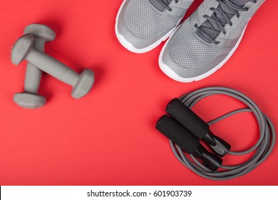 Sport shoes, dumbbells and skipping rope on red background. Top view. Fitness, sport and healthy lifestyle concept.