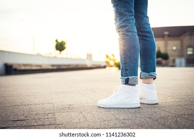Sport shoes. Girl in blue jeans and white high tops standing on the ground