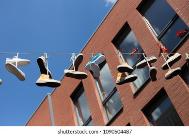 Sport shoes are hanging on a line in a city. The symbol of the Four Days March (vierdaagse of 4daagse loop) in Nijmegen, The Netherlands. July 2017.