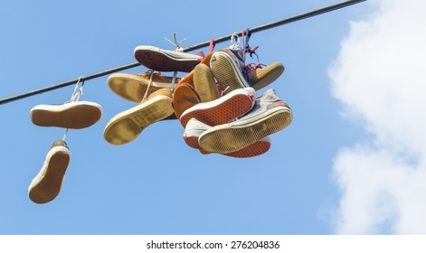 sport shoes are hanging over the thick wire.