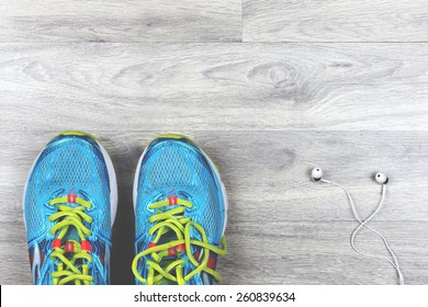 Sport shoes and headphones on a wood floor